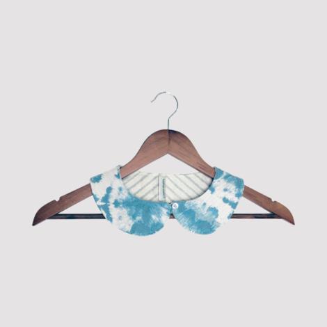 cuello de quita y pon de tela estampada en azul turquesa y blanco en percha